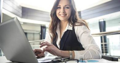 Young business woman working on a laptop in a modern office - women in business