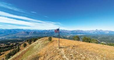 Forest Service and American flag flying over dramatic landscape view of the Absaroka Mountains just outside of Yellowstone National Park - Energy2016 - Elected Leaders Impact our Energy Industry