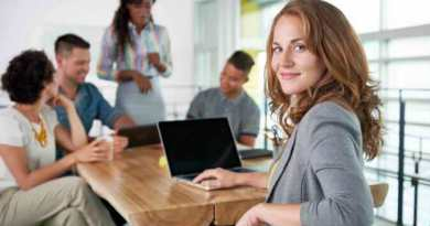 Image of a succesful casual business or industry woman using laptop during meeting