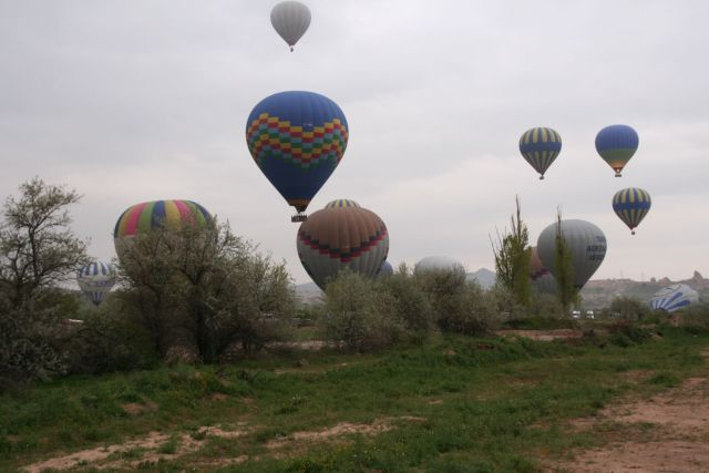 Cappadocia hot air balloons lifting off on a foggy morning.