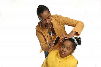 black mother brushing daughter's hair
