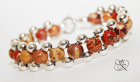 Painted round wooden beads accented with smaller silver plated beads framing the design.