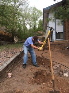 Shane works to make tree holes for front driveway.