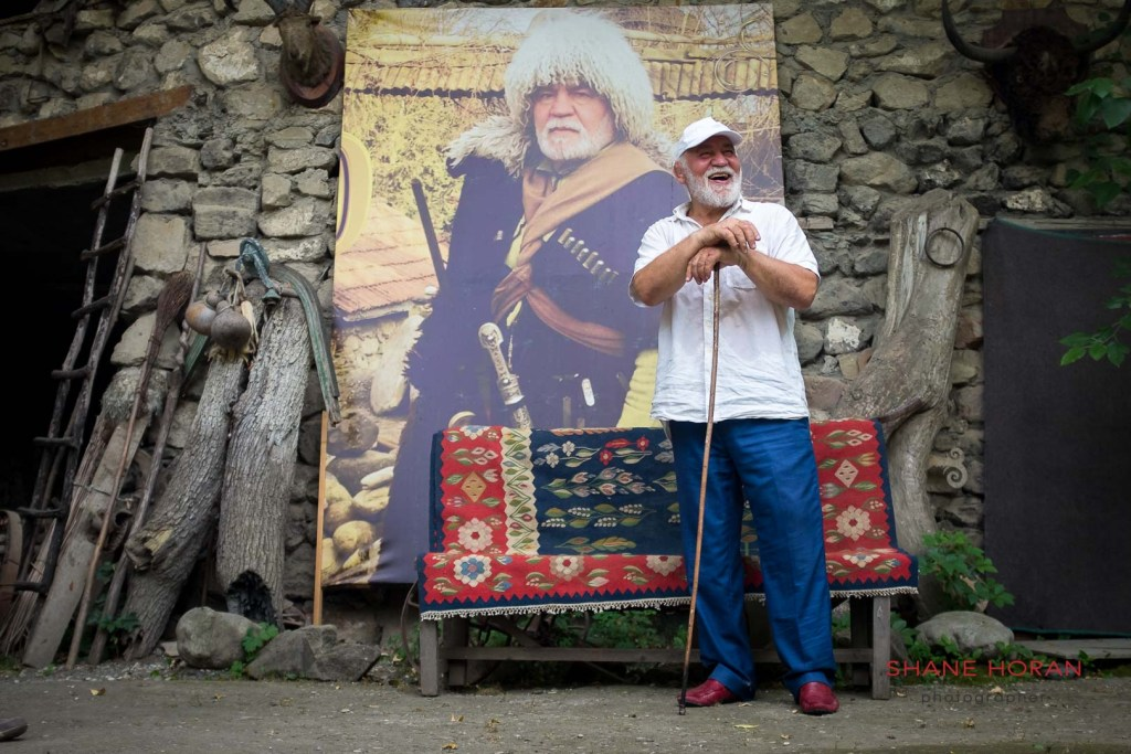 Chechen man Adem Satuev poing next to a blown up portrait of himself at his home in Chechnya, Russia