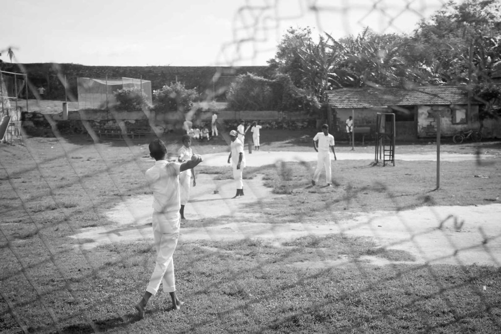 Youths play a game of cricket in a Galle park, Sri Lanka