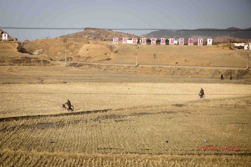 North Korean villagers make their way through a field