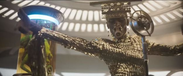 star wars solo super bowl trailer performer in gold with mic and mouthpiece and creature in glass jar