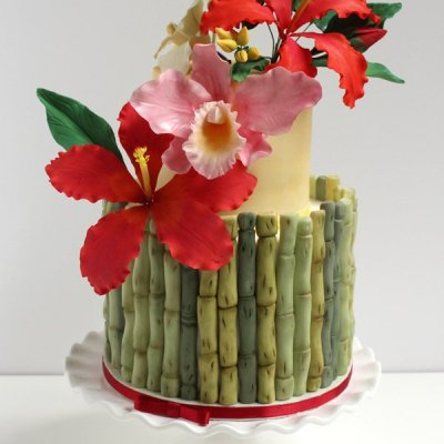 Tropical flowers wedding cake with bamboo, hibiscus and orchids