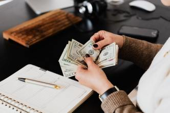 A woman counting money at her desk with a notebook and pen. This is one of the sacrifices Entrepreneurs Will Have to Make.