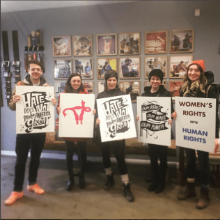 The ADX staff and volunteers going to teh womens march with sweet lazer-cut signs!