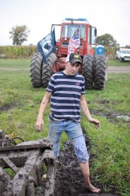 Logan Douglas, age 16, walks back to his truck after hooking up the truck to the tractor for his Step Father, Doug Jarman, to tow him out of a mud pit in Farwell, Mich. on Friday Oct. 4, 2013.