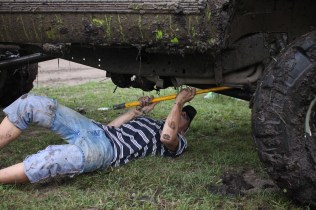 Logan Douglas, age 16, scrapes mud off the starter of his truck in Farwell, Mich. on Friday Oct. 4, 2013.