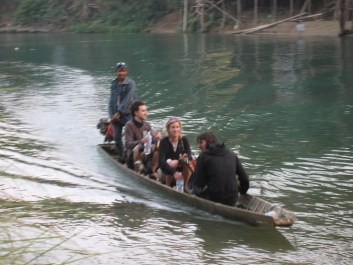 Taking a boat over to the rock climbing spot near Vang Vieng