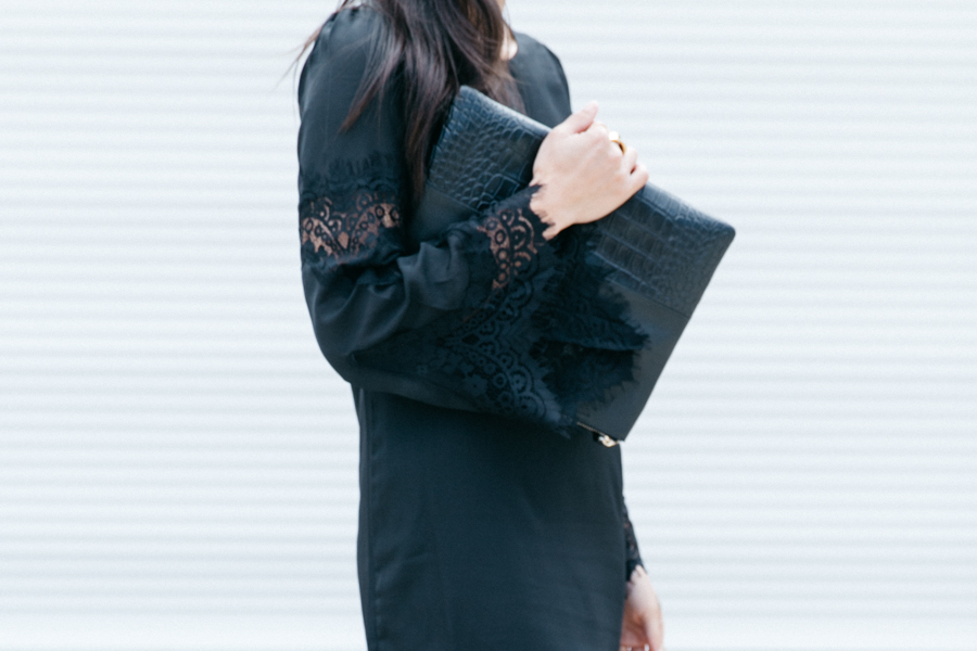 Black lace outfit & black leather clutch.