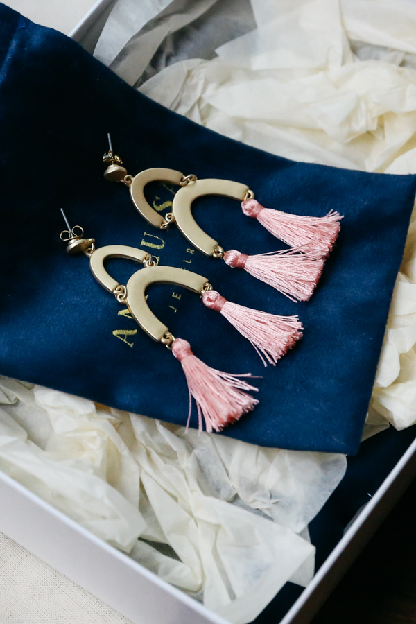 Pink and gold earrings with tassels.