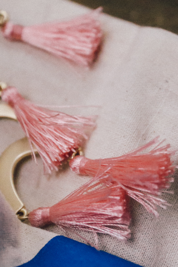 Gold earrings with pink tassels.