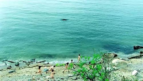 actors running along the beach naked for the gobbledigook video