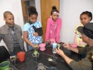 Children looking intently at their gardening instructor