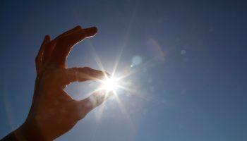 Mano que parece sujetar el sol entre el pulgar y el índice. (© AP Images)