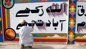 Hombre pinta palabras en urdu sobre una pared (© AP Images)