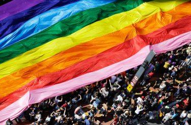 Participantes a un desfile llevan una bandera del arco iris (© AP Images)