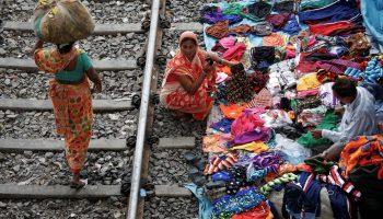 Mujer con una carga en la cabeza camina junto a unas personas que venden telas al lado de unas vías ferroviarias (© Rupak De Chowdhuri/Reuters)