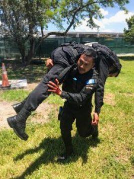 Hombre uniformado cargando a otro hombre uniformado (© Sargento Oscar D. Pla, Departamento de Policía de Miami-Dade)