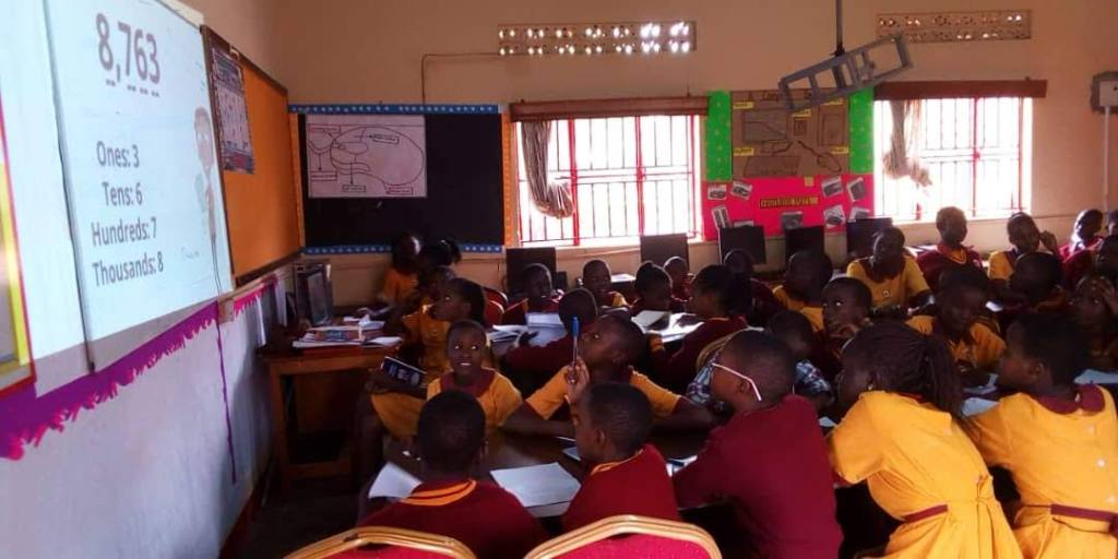 Learners of Dream Africa Primary schools using a projector during a mathematics lesson, Kampala Uganda
