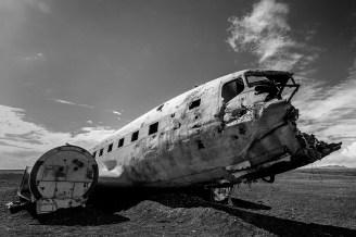 Flugzeugwrack inmitten einer schwarzen Wüste