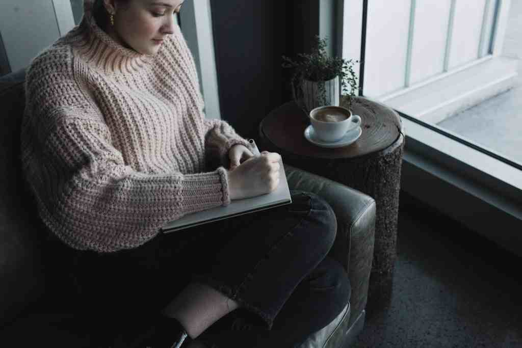 a woman journaling with a coffee