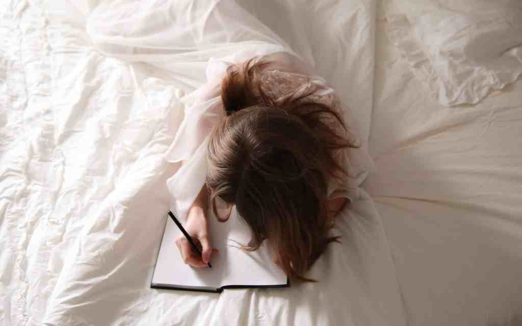 a woman journaling in bed