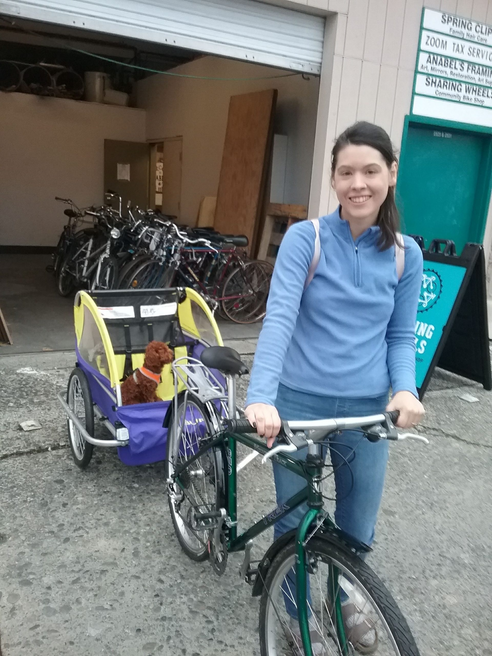 woman holds bike towing a trailer with a small dog in it