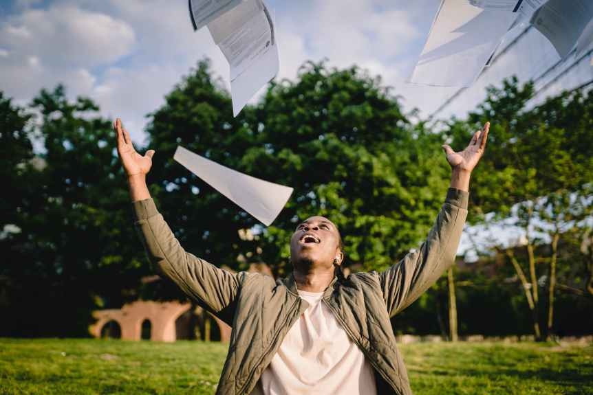 happy student throwing papers in air in park