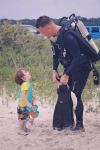 Diver looking down at kid on the beach