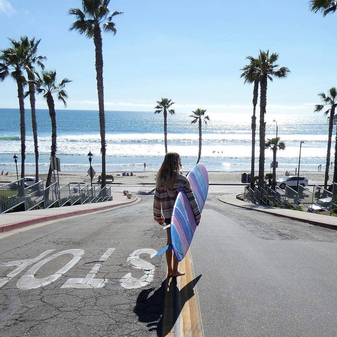 Shark Tooth Surf Co Team Rider Avalon Besso heading to the beach for a surf session
