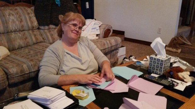 The bride's mother still smiling while helping with the invitations