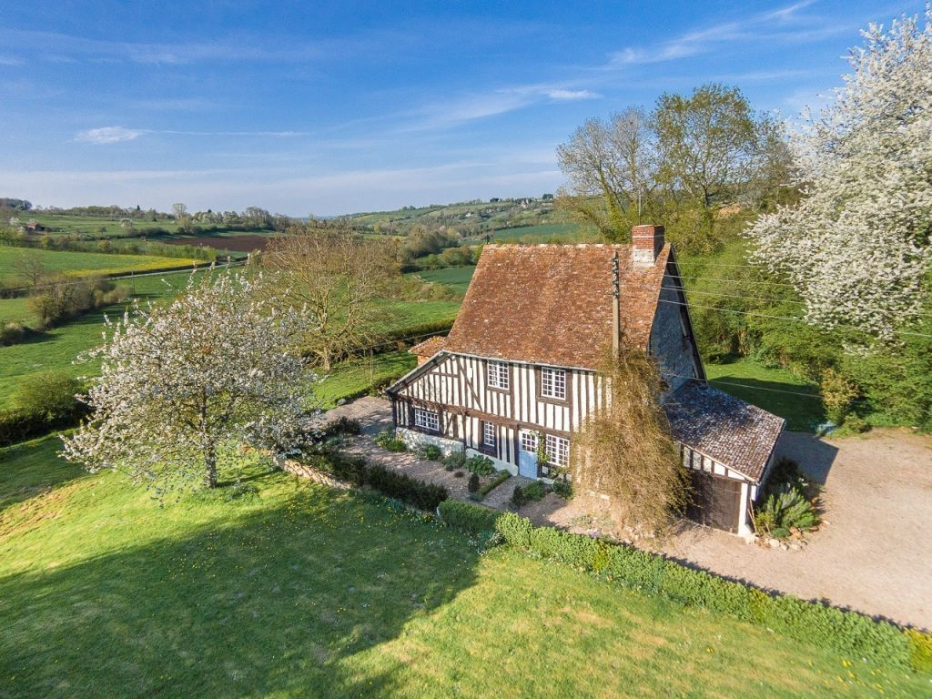 timbered cottage in rolling green countryside