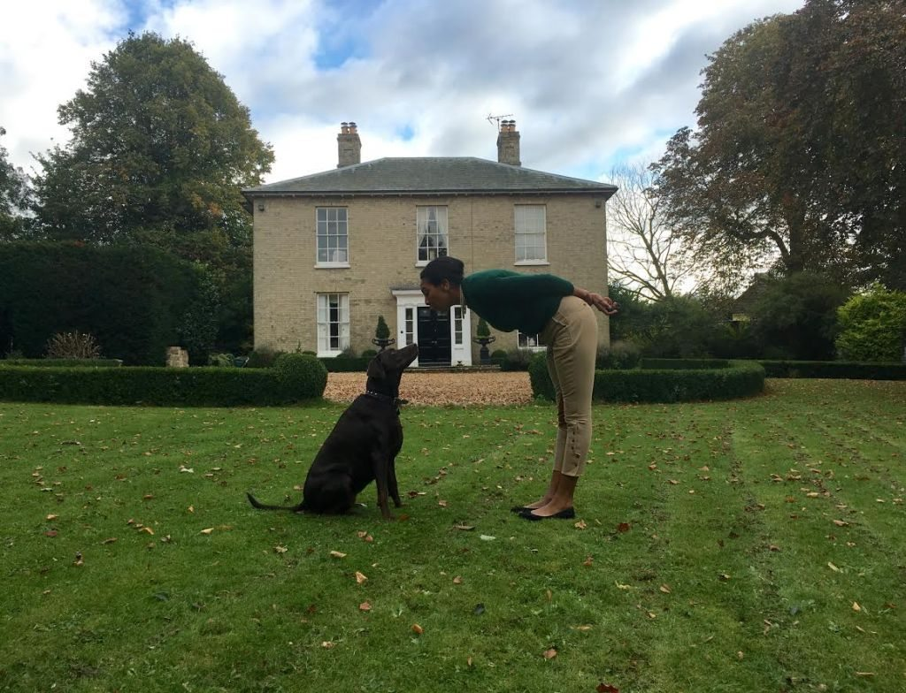 lady and dog in front of house