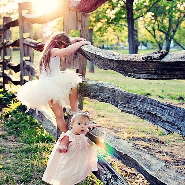 little girls playing on fence