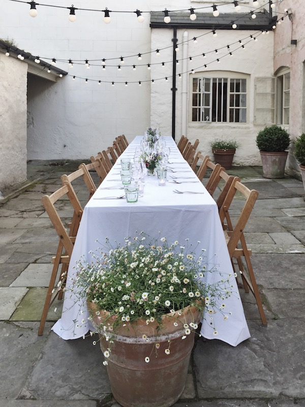 white table set outside with wood chairs