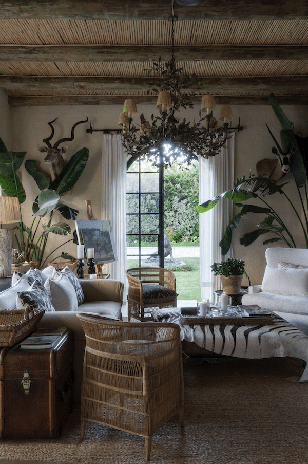 living room decorated with plants, chandelier, white couches and wicker furniture