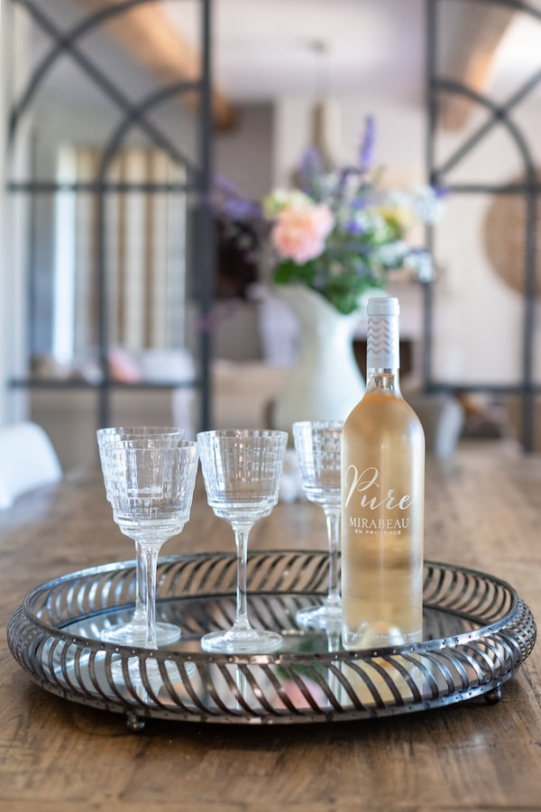 three wine glasses and bottle of rose on tray
