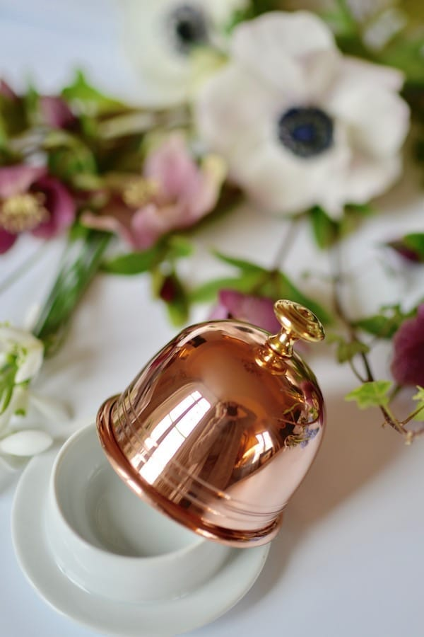 copper butter dish in front of flowers