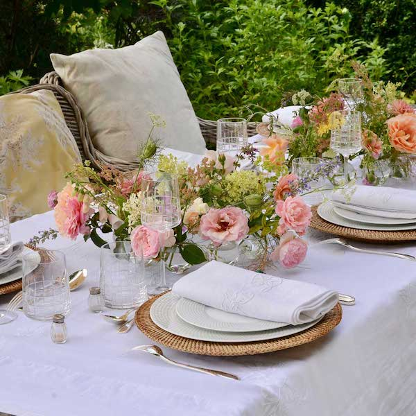 outdoor tablescape with plates, napkins and flowers