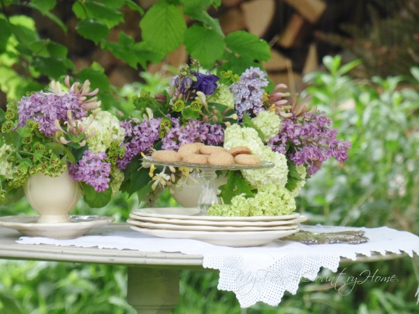 table laid for tea with flowers arrangement and pile of plates