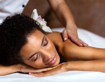 Beautiful young woman having a back massage at health spa.
