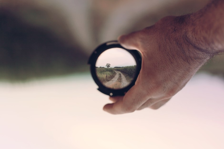 hand holding a lens clarifying a path