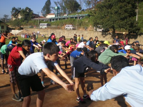 The students participate in a physical education lesson at the local grounds. The warm-up is old school calisthenics. Love it!