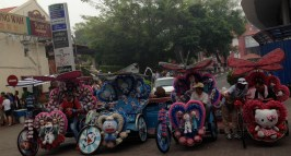 The bike rickshaw drivers await their next fares in their tricked out rides.