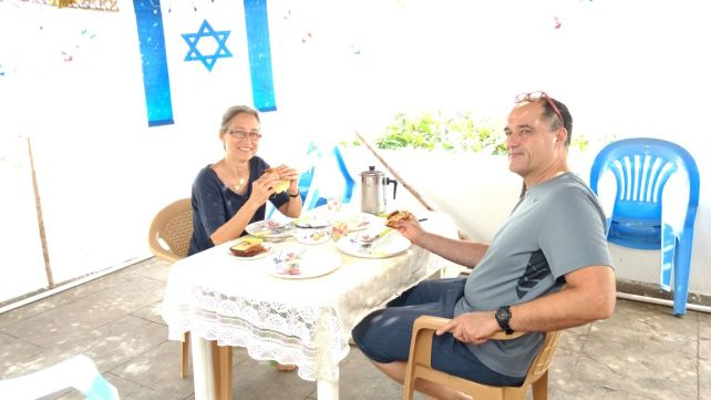 Rachel and Zvi eat in sukka